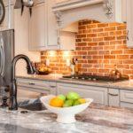 Kitchen with marble countertop island and brick backsplash