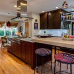 Natural wood cabinet kitchen with custom shelving over wood island