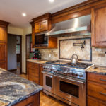 Natural wood cabinets with stone backsplash