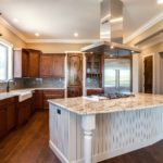 Natural wood cabinet kitchen with large center island with stove hood