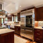 Dark wood cabinet kitchen with large stainless steel refrigerator