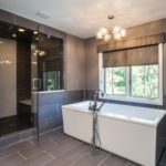 Large soaking tub and standing shower with dark tile